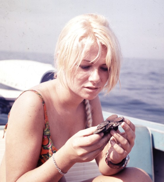 Kathy examines tea token coins solidified into a clump. (1967)